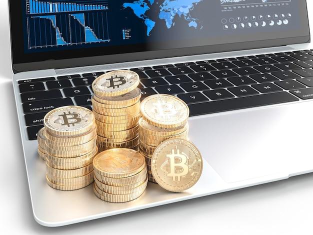 Pièces d'or bitcoin sur un ordinateur portable moderne avec tableaux financiers Photo Premium