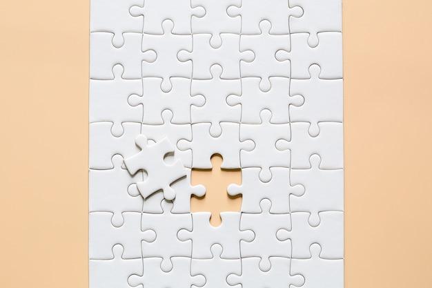 Pièces de puzzle blanc sur rose Photo gratuit