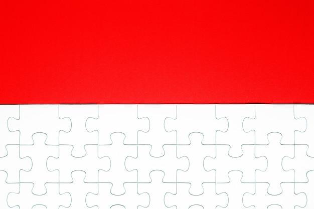 Pièces de puzzle blanches sur fond rouge séparées Photo Premium
