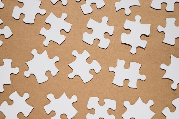 Pièces de puzzle sur fond de papier brun Photo gratuit