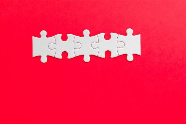 Pièces De Puzzle Sur Fond Rouge. Fond D'affaires. Photo Premium