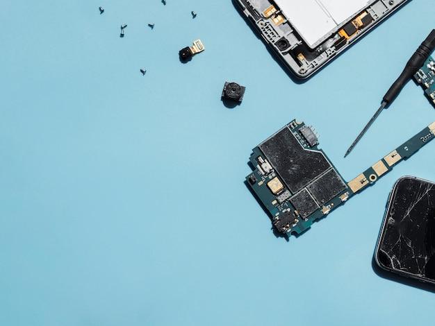 Pièces de téléphone sur fond bleu Photo gratuit
