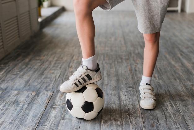 Pied De Garçon Sur Un Ballon De Foot Sur Le Plancher De Bois Franc Photo gratuit