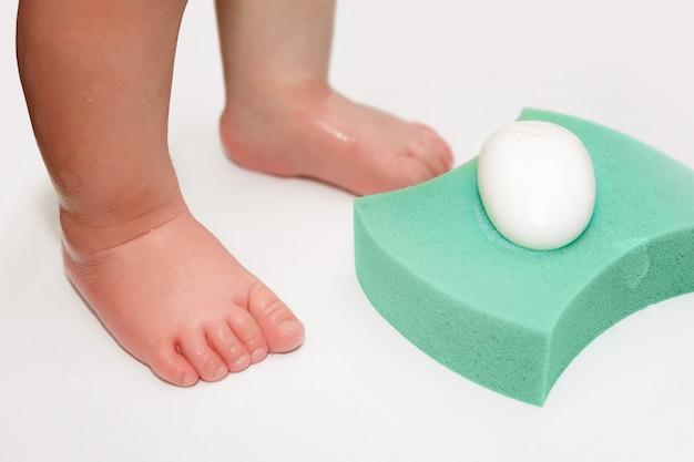 Pieds de bébé, éponge et savon dans la baignoire Photo Premium