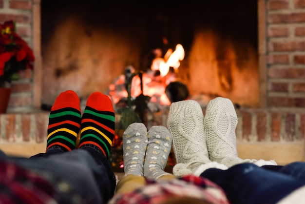Les Pieds Dans Des Chaussettes De Noël Près De Cheminée De Détente à La Maison Photo gratuit