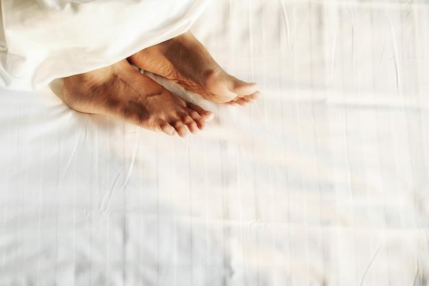 Pieds dans un lit sous une couverture blanche. pieds nus d'une femme qui jette un coup d'œil sous la couverture. Photo Premium