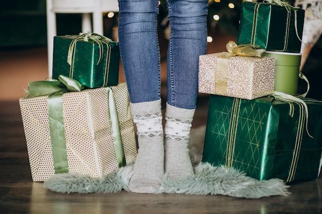 Pieds féminins en chaussettes avec un cadeau de noël tout autour Photo gratuit