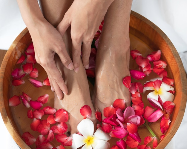 Pieds féminins et les mains dans un bol en bois avec des fleurs au salon spa. Photo Premium