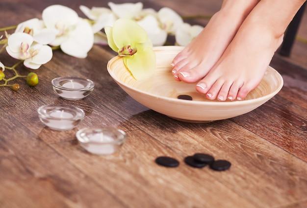 Pieds féminins manucurés dans un bol en bois spa avec des fleurs et de l'eau closeup Photo Premium