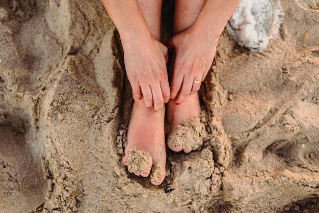Pieds de femme dans le sable d'une plage Photo Premium