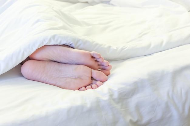 Pieds de femme endormie dans la chambre blanche Photo Premium
