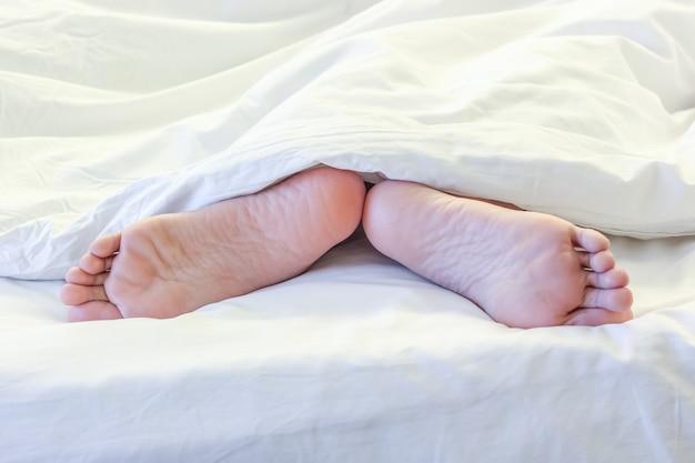 Pieds de femme endormie dans une chambre blanche Photo Premium