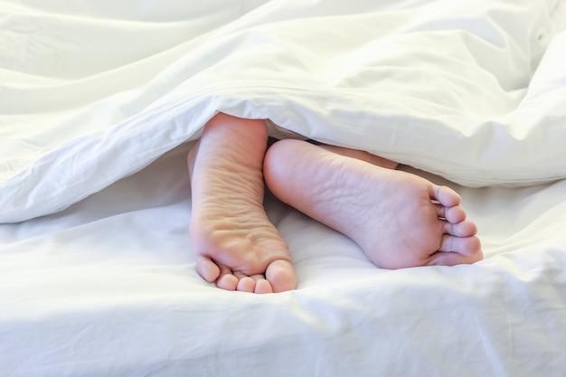 Pieds De Femme Endormie Dans La Chambre à Coucher Blanche Photo Premium