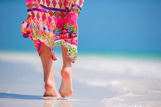 Pieds de femme sur la plage de sable blanc en eau peu profonde Photo Premium