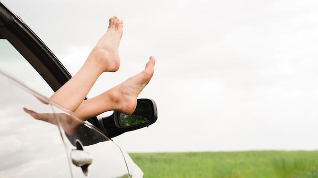 Pieds de femme regardant par la fenêtre de la voiture Photo gratuit