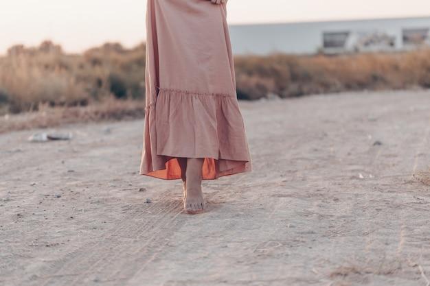 Pieds d'une femme en robe rose marchant sur le sable pendant le coucher du soleil Photo Premium