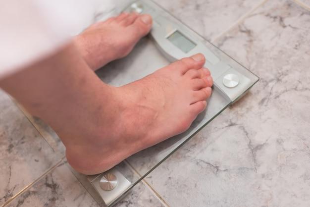 Pieds d'homme debout sur une balance Photo Premium