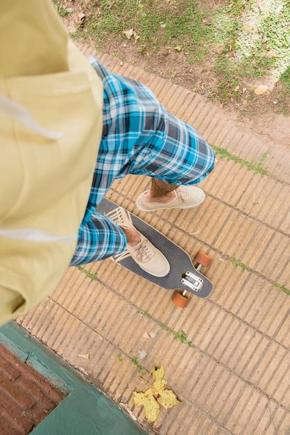 Pieds d'un homme debout sur un longboard Photo gratuit