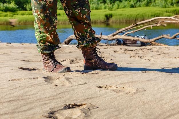 Pieds d'hommes en bottes au bord de la rivière Photo Premium