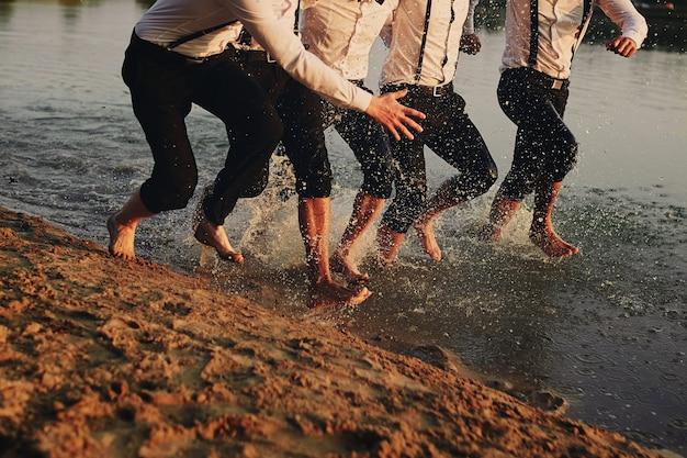 Les pieds des hommes dans l'eau. les hommes courent sur l'eau. été. groupe de heureux jeune homme pieds éclaboussures Photo Premium