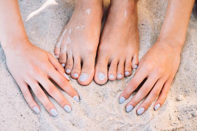 Pieds et mains féminins avec manucure dans le sable de la plage en été Photo Premium