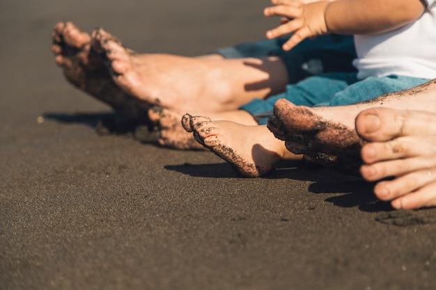 Pieds de parents et bébé assis sur une plage de sable fin Photo gratuit