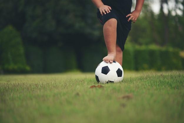 Pieds de petit garçon tenant le football au champ d'herbe Photo gratuit