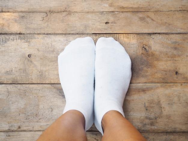 Pieds portant des chaussettes blanches sur bois Photo Premium