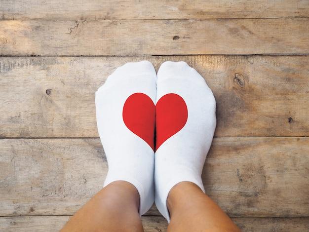 Pieds portant des chaussettes blanches en forme de cœur rouge Photo Premium