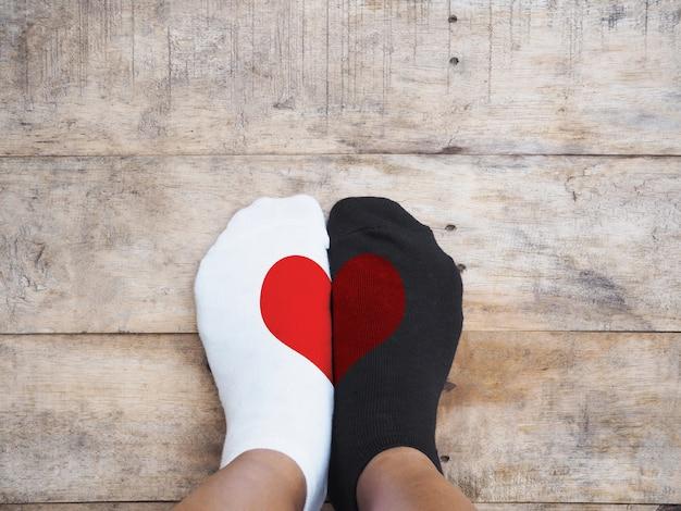 Pieds portant des chaussettes blanches et noires avec une forme de coeur rouge Photo Premium
