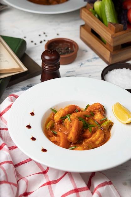 Pieds de poulet à la sauce tomate dans un bol blanc avec des légumes et du citron. Photo gratuit