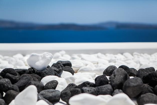 Pierre blanche en forme de coeur sur un fond de mer et ciel bleu Photo Premium