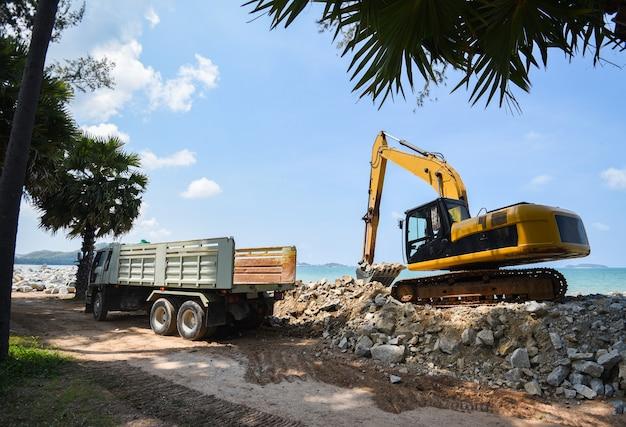Pierre pelle excavatrice et camion à benne basculante travaillant sur un chantier de construction Photo Premium