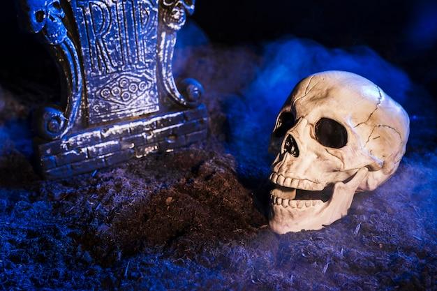 Pierre tombale près du crâne au sol Photo gratuit