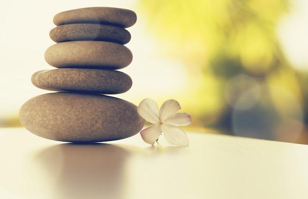 Pierres de massage spa et fleur de gardénia blanche Photo Premium
