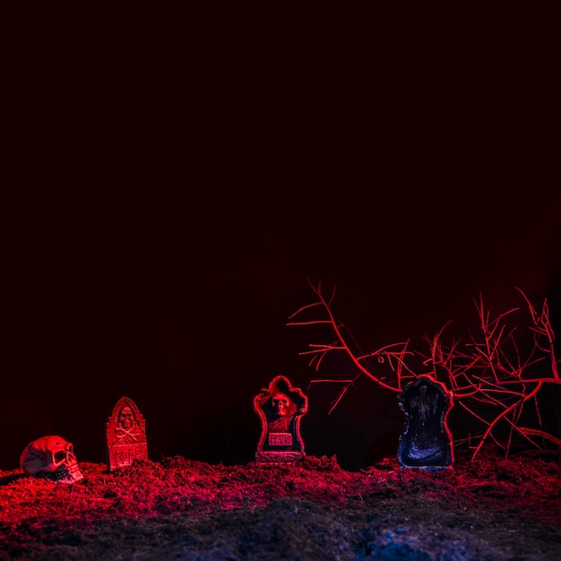 Pierres tombales et crâne éclairés par une lumière rouge au sol Photo gratuit