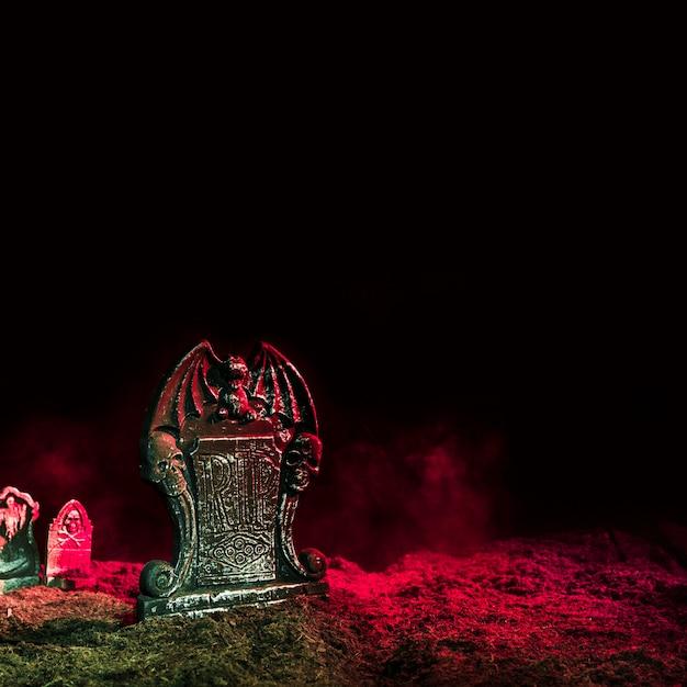 Pierres tombales illuminées par une lumière rose au sol Photo gratuit