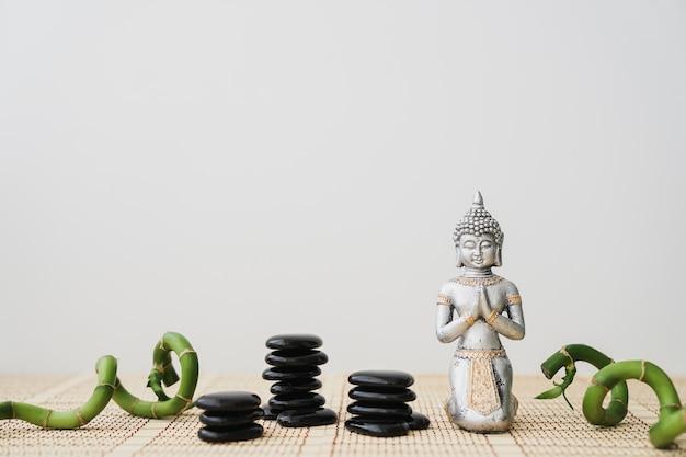 Pierres volcaniques, bâtons de bambou et personnage de bouddha Photo gratuit