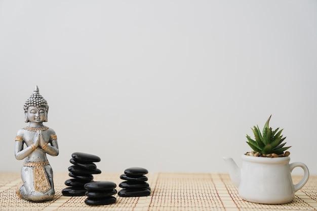 Pierres volcaniques, bouddha et pot de fleurs Photo gratuit