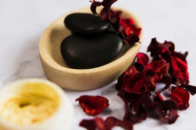 Pierres zen noires dans un récipient en marbre avec des pétales d'orchidées rouges secs Photo gratuit