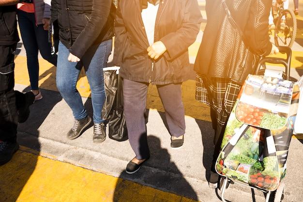 Les piétons traversant la route avec des sacs Photo gratuit