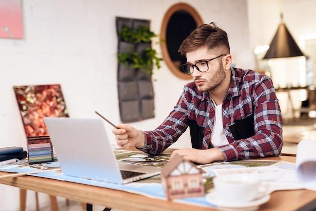 Pigiste homme dessin sur plan à l'ordinateur portable assis au bureau. Photo Premium