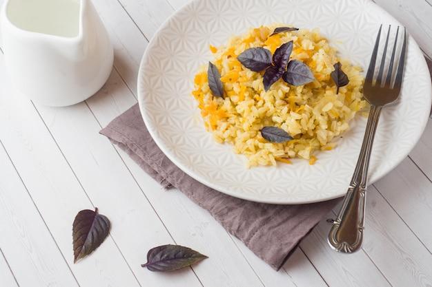 Pilaf traditionnel, riz aux légumes et basilic frais dans une assiette sur une table en bois clair. Photo Premium