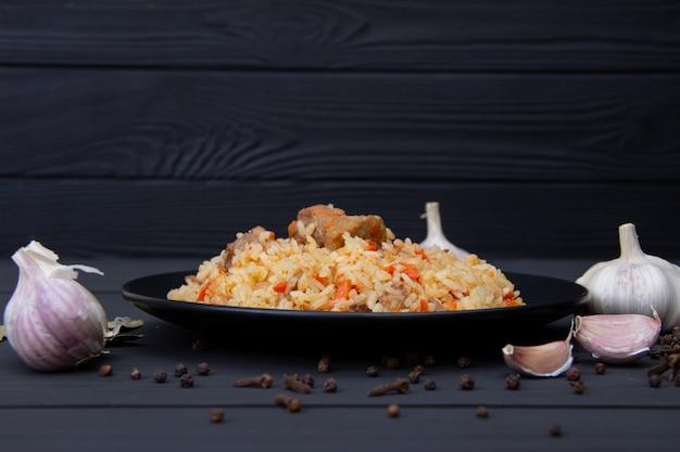 Pilaf traditionnel savoureux à l'ail et aux épices sur plaque noire. plat national ouzbek. Photo Premium
