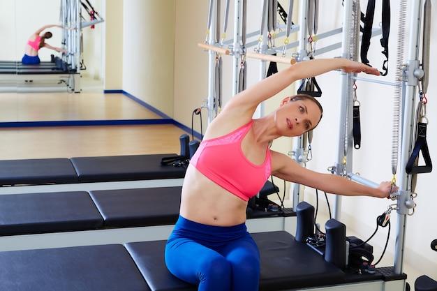 Pilates réformatrice côté femme à travers l'exercice Photo Premium