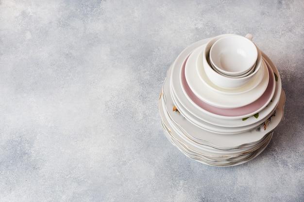 Pile d'assiettes propres vides sur une table grise avec espace de copie. Photo Premium