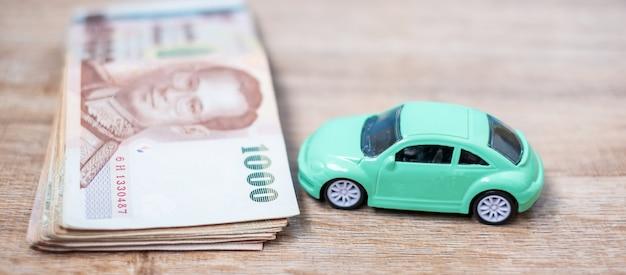 Pile de billets de baht thaïlandais avec voiture. Photo Premium