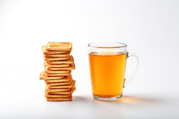 Une pile de biscuits au blé doré et une tasse de thé vert parfumé sur fond gris Photo Premium