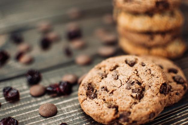 Une pile de biscuits à l'avoine avec des morceaux de chocolat et des fruits confits se trouve sur une table en bois Photo Premium