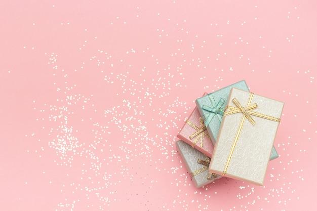 Pile de boîtes-cadeaux de couleurs pastel sur fond rose, vue de dessus espace de copie Photo Premium